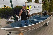 Robert Hayes kneels in the boat that he won during the Downtown Soup Kitchen's Slam'n Salm'n Derby after he caught a 40.97-pound king salmon June 15, 2008.